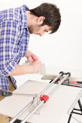 Home improvement - handyman cut tile Stock Photos