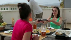 Female friends with tablet computer celebrating dinner on the terrace Stock Footage