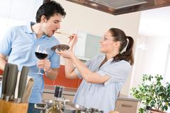 Happy couple cook in kitchen tasting food Stock Photos