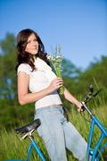 woman with old-fashioned bike and summer flower - stock photo
