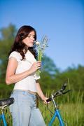 Woman with old-fashioned bike and summer flower Stock Photos