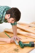 Home improvement - handyman installing wooden floor Stock Photos