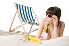 beach - woman in bikini with drink and flip-flop on sand - stock photo