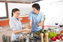 young happy couple cooking in kitchen - stock photo