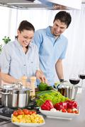 smiling couple drink red wine cooking in kitchen - stock photo