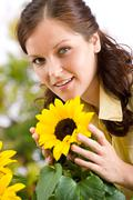 portrait of beautiful woman with sunflowers - stock photo