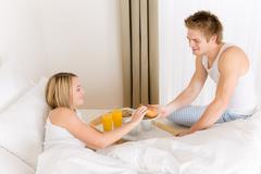 luxury hotel honeymoon breakfast - couple in bed - stock photo