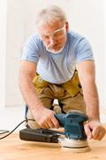 home improvement - handyman sanding wooden floor - stock photo