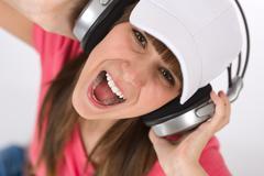 female teenager singing with headphones - stock photo