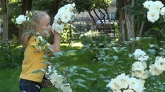 Child Smelling and Playing with White Roses in the Garden Stock Footage