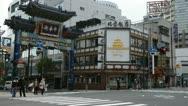 Cars Passing People Walk Crossing Busy City Street Yokohama Japan Chinatown Gate Stock Footage