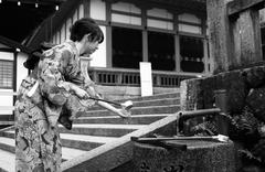 Young woman in Yukata reaching for drinking water at Nijojo Temple in Kyoto Stock Photos