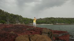 Young man casting off rocks while fishing at Bittangabee Bay, Australia - stock footage
