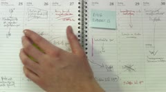 A hand browsing through an agenda with post-it notes Stock Footage