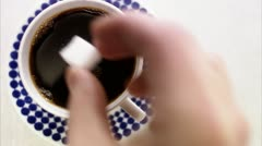 Adding a lump of sugar to a cup of coffee Stock Footage