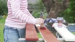 A woman painting plank Stock Footage