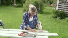A woman doing carpentry in a garden Stock Footage