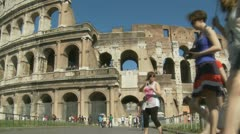 Dozens tourists pass Colosseum.slo mo zoom out - stock footage