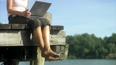 A woman using a laptop on a jetty by a lake Stock Footage
