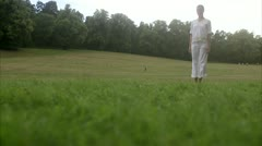 A woman turning cartwheels in a park outside Stock Footage