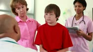 Doctor talking to young patient and grandmother Stock Footage