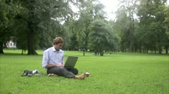 A man in a park using a laptop Stock Footage