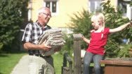 Girl and senior man recycling newspapers Stock Footage