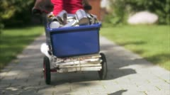 Girl with cans on a three-wheeler Stock Footage