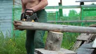 Stock Video Footage of Mature man with chainsaw cutting the log