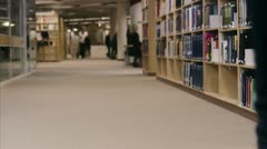 Two students walking arm-in-arm in a library Stock Footage