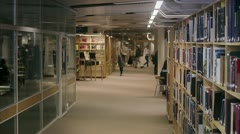 Students walking arm-in-arm in a library Stock Footage
