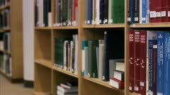 Female student looking for literature in a library Stock Footage