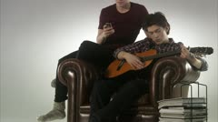 Two teenage boys playing the guitar - stock footage