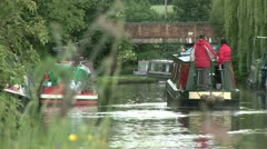 Two people sailing a narrow boat Stock Footage