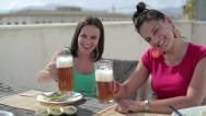 Female friends drinking beer on the terrace Stock Footage
