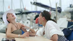 Two laughing women drinking wine near marina, steadycam shot Stock Footage