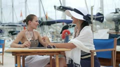 Two women looking at handsome man at marina, steadycam shot Stock Footage