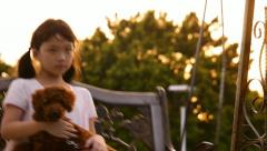 Asian kid and poodle dog swinging - stock footage