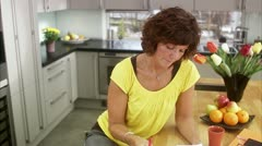 MS TD Mature woman calculating bills in kitchen / Stockholm Stock Footage