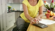 MS TU Mature woman calculating bills in kitchen / Stockholm Stock Footage
