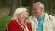 Senior couple on a bench in the forest Stock Footage