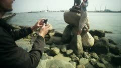 MS TU Young man photographing woman standing by Little Mermaid statue Stock Footage