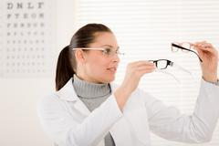 Optician doctor woman with glasses and eye chart Stock Photos