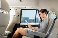 Stock Photo of executive businesswoman in car work touch tablet