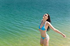 summer beach woman in bikini swim water - stock photo