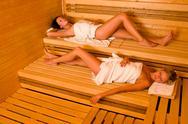 Sauna two women relaxing lying wrapped towel Stock Photos
