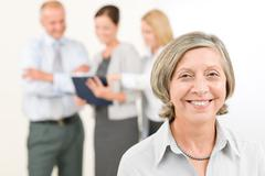 business team senior woman with happy colleagues - stock photo