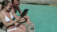 Young couple with digital tablet sitting by the sea HD Stock Footage