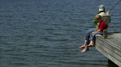 A father and his son sitting on a jetty fishing - stock footage