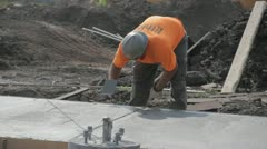 Stock Footage - Construction worker spreads cement by hand - Med close - stock footage